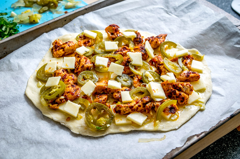 This Spicy Chicken and Pickled Jalapeno Pizza is the perfect example of Mexican cooking ingredients influencing just about everything in my kitchen. A super easy and delicious recipe with no special pizza gear needed! mexicanplease.com