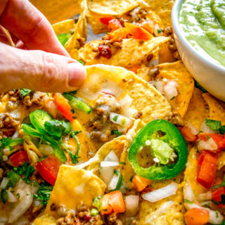 These Spicy Ground Beef Nachos have the potential to save your day. Chipotles in adobo give the beef real kick and when loaded on cheese covered tortilla chips they quickly become a go-to meal. Served with a homemade Avocado Salsa Verde and your choice of fixings. So good! mexicanplease.com