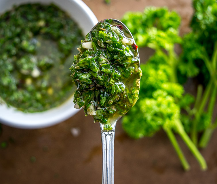 I'm using chili powder and cayenne to give a traditional chimichurri sauce some real kick! This version really shines when served with some homemade empanadas. So good! mexicanplease.com