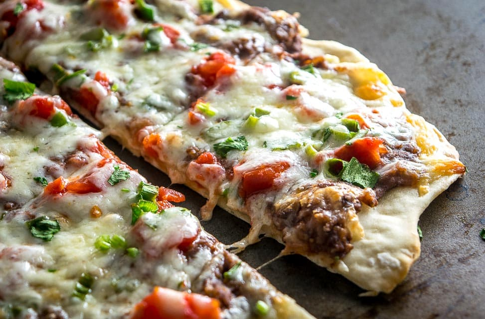 This Spicy Black Bean Pizza relies on a delicious black bean puree and a thin layer of garlic oil to create a vegetarian delight. So good! mexicanplease.com