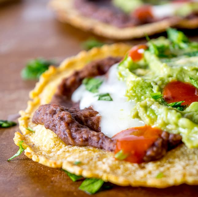 Serious reward to effort ratio in these tostadas! We're crisping a corn tortilla and loading it up with spicy black bean puree and a refreshing guacamole. So good! mexicanplease.com