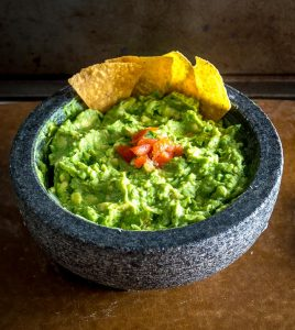 We're grinding an onion-jalapeno-cilantro paste in a molcajete for a delicious batch of homemade guacamole. Don't forget a final squeeze of lime, so good! mexicanplease.com