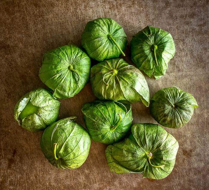 fresh tomatillos on cutting board