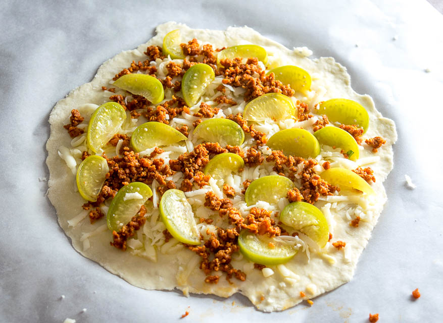 This is my new favorite pizza! The pickled tomatillos pair well with the chorizo and we're using a garlic oil layer as the sauce -- so good! mexicanplease.com