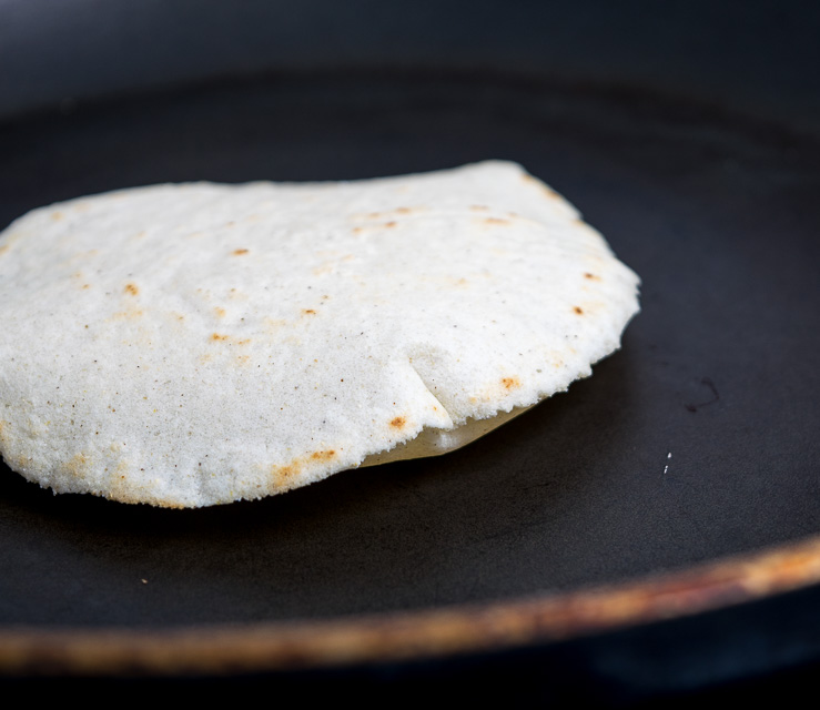 Corn tortilla puffing up in a small skillet.