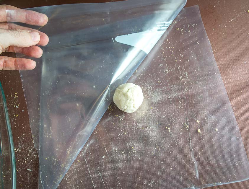 Placing dough ball between ziploc sides.