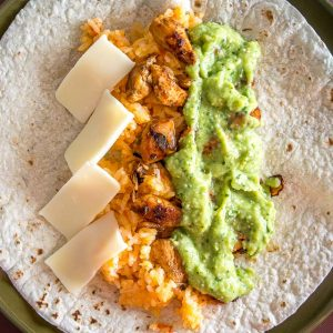Put some Avocado Salsa Verde in your burritos and everything beyond that is a bonus! I added chicken, Mexican rice, and cheese to this batch -- yum!! mexicanplease.com