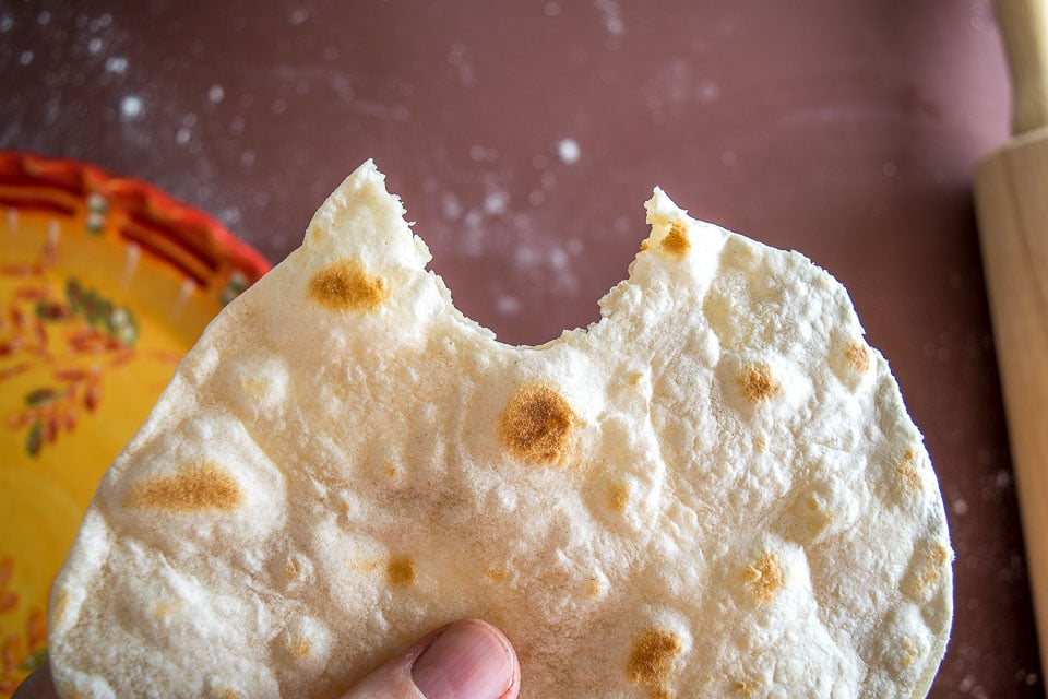 Taking a bit out of a homemade flour tortilla.