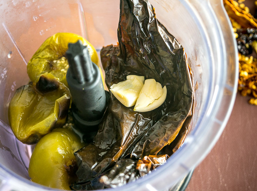 Adding tomatillos and pasillas to a blender for salsa