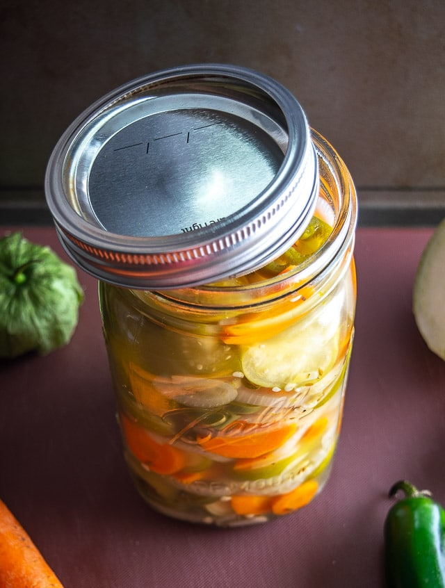 Quart sized Mason jar of pickled jalapenos, tomatillos, onions, and carrots.