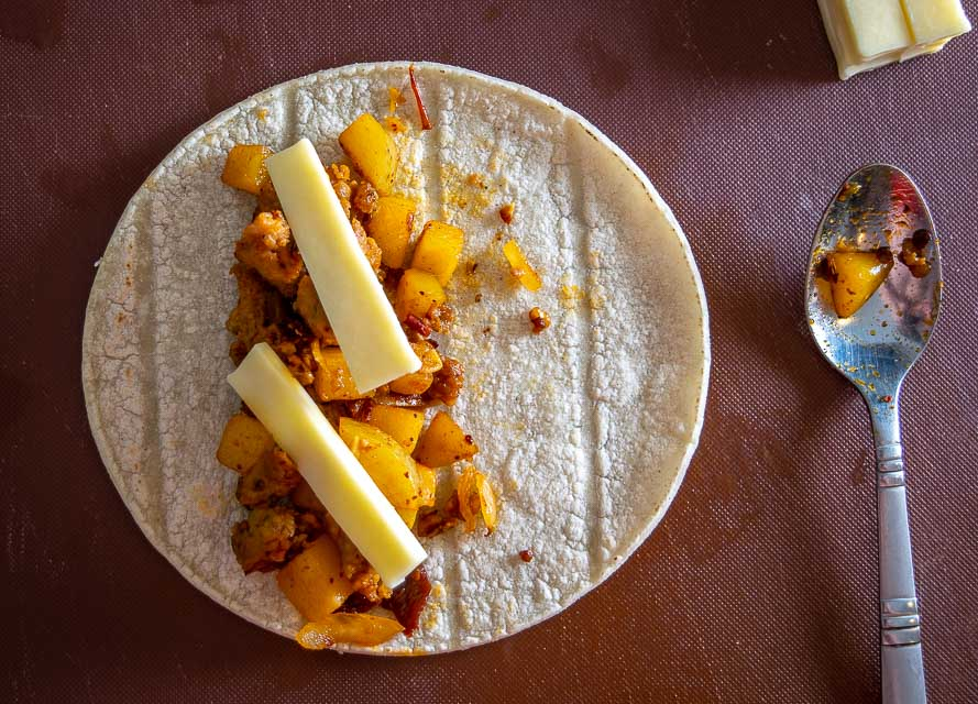 Adding Papas con Chorizo to warm corn tortilla