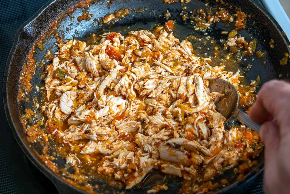 Combining 1/2 cup Tinga sauce with shredded chicken