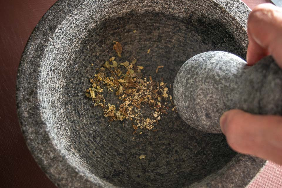 Crushing spices in the molcajete