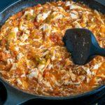 Adding shredded chicken to the Tinga sauce