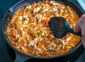 Adding shredded chicken to the Tinga sauce