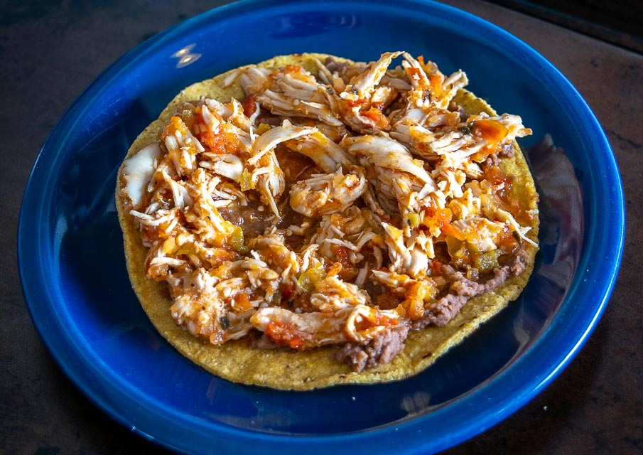 Adding Tinga de Pollo to the tostada