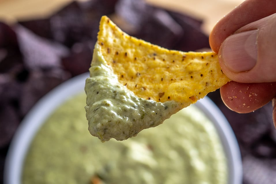 Dipping a chip in Roasted Poblano Queso Dip