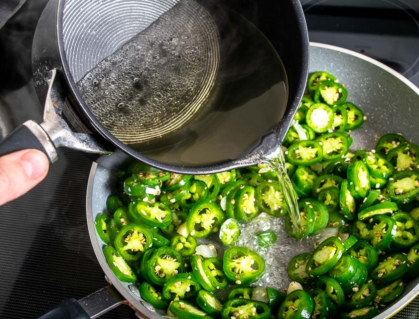 Adding the sugar vinegar mixture to the jalapenos