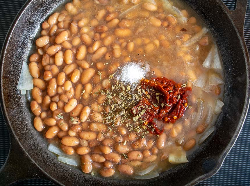 Adding spices to the cooked Peruano beans