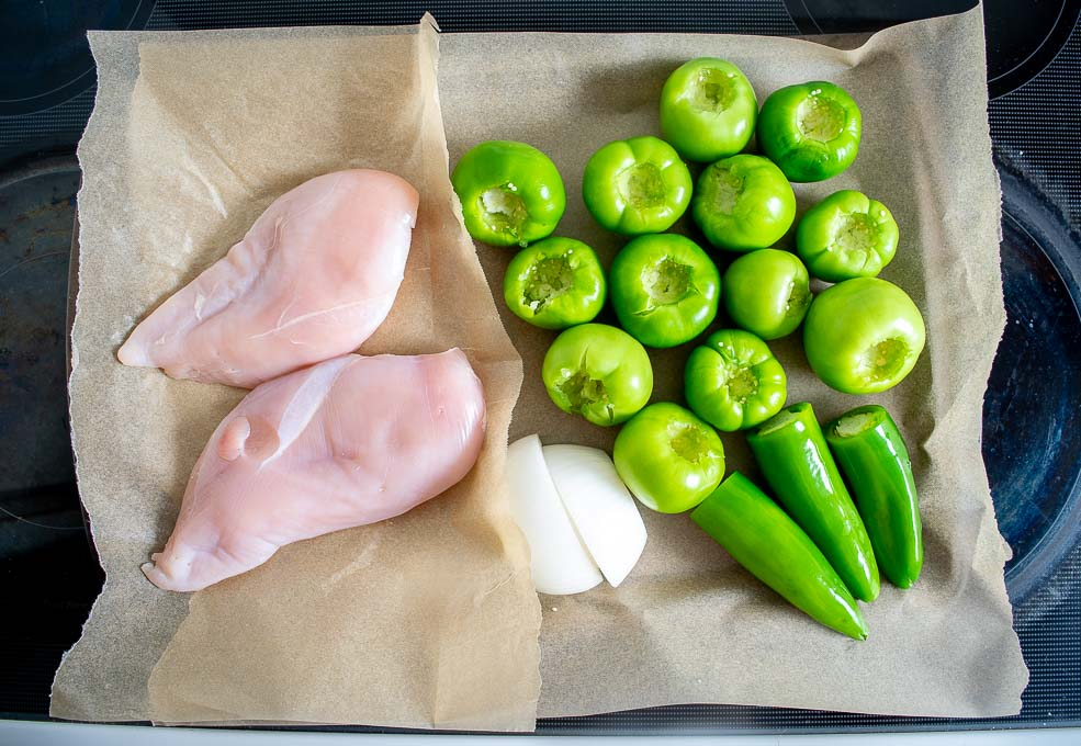 Adding chicken and tomatillos to baking sheet for roasting