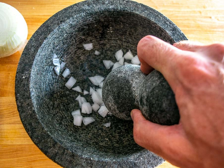 Grinding onion and salt in a molcajete