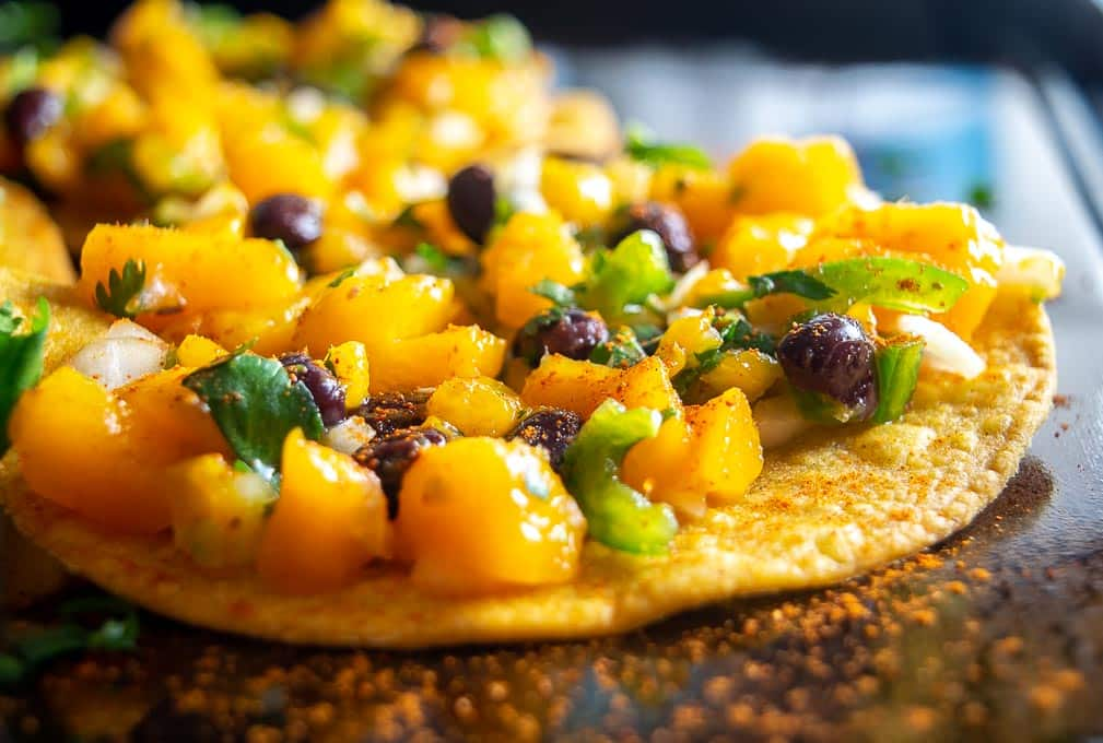 Adding chile powder to Mango Black Bean tostada