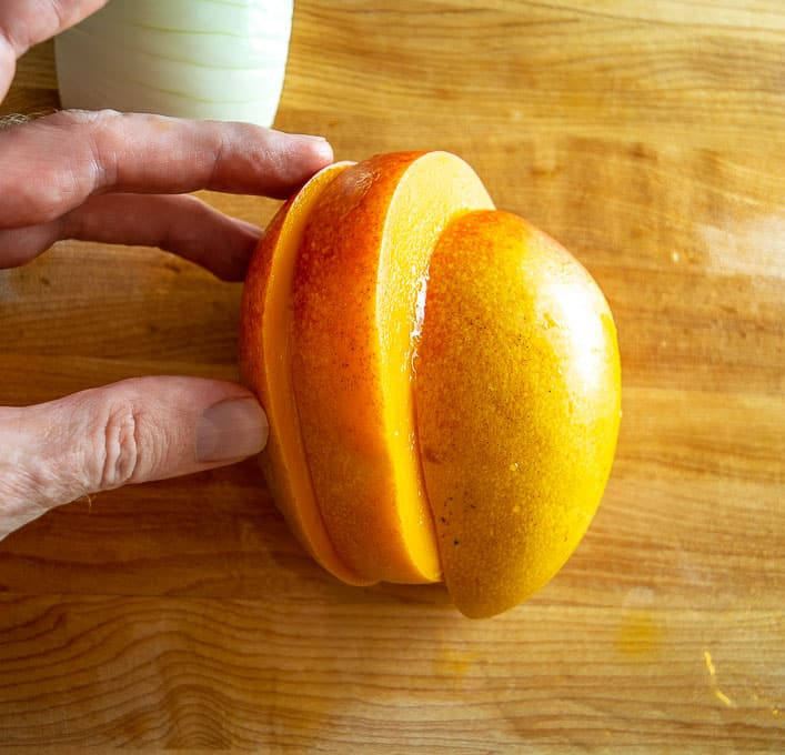 Cutting a fresh mango into three parts