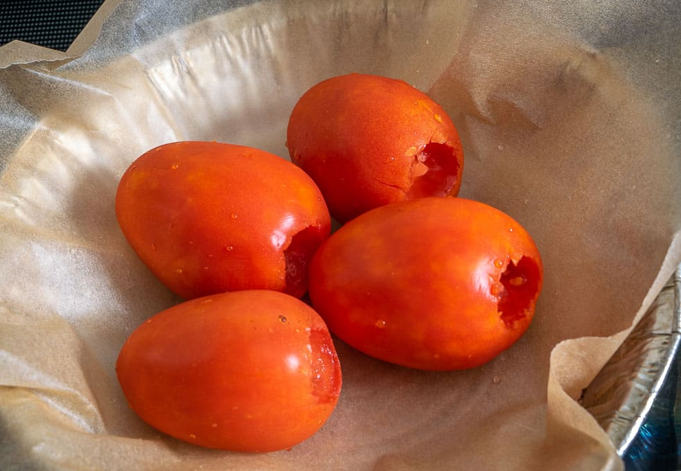 Roasting four tomatoes for the broth