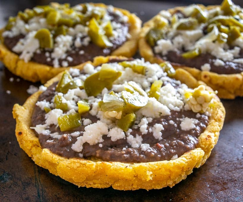 Sopes topped with pickled jalapenos, Queso Fresco, and refried beans.