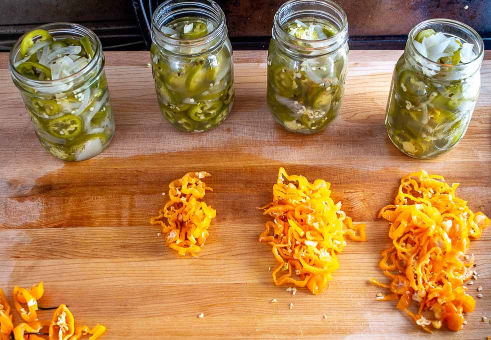 4 pint sized jars of Pickled Jalapenos along with chopped Habaneros