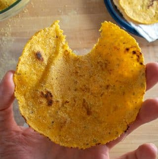 Taking a bite of corn tortilla after cooking