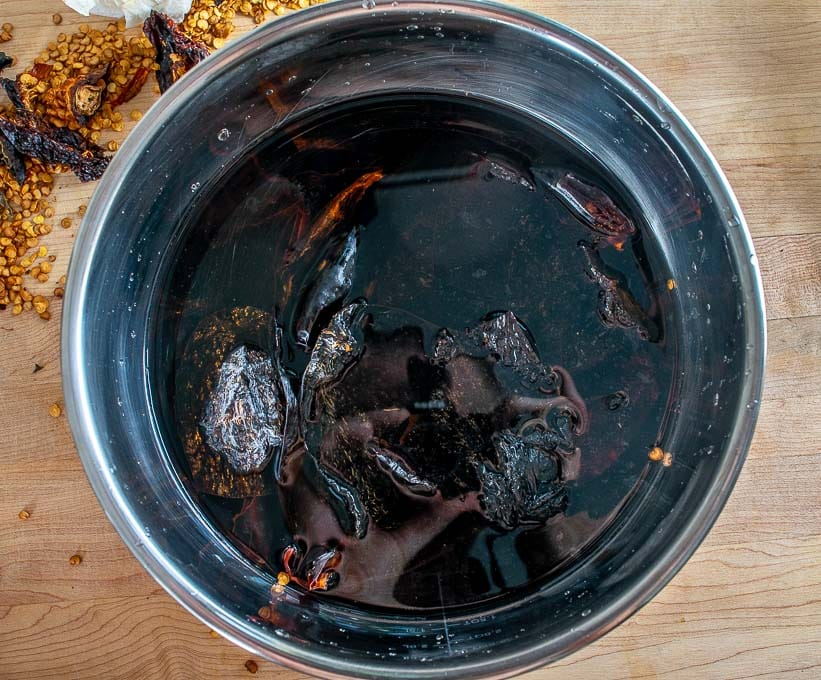 Letting the dried chiles reconstitute in hot tap water