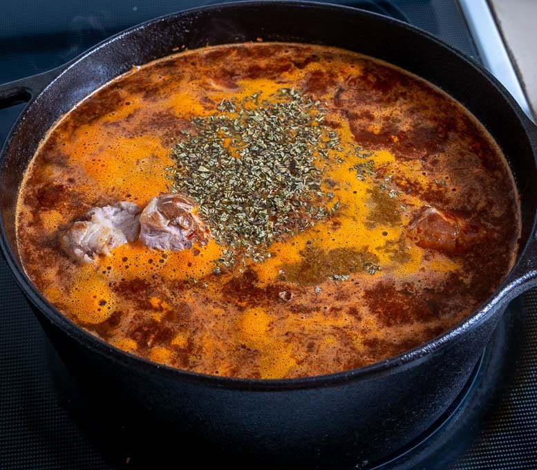 Adding spices to the Pozole before simmering