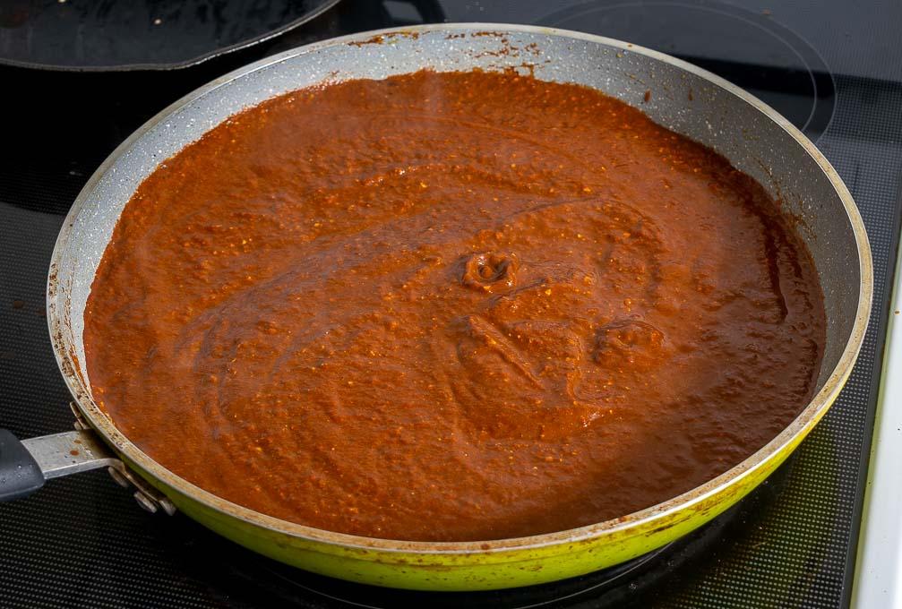 Adding Mole sauce to a large saucepan