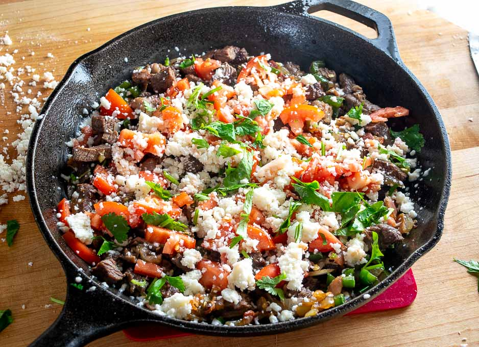 Topping with Queso Fresco, tomatoes, cilantro and lime juice