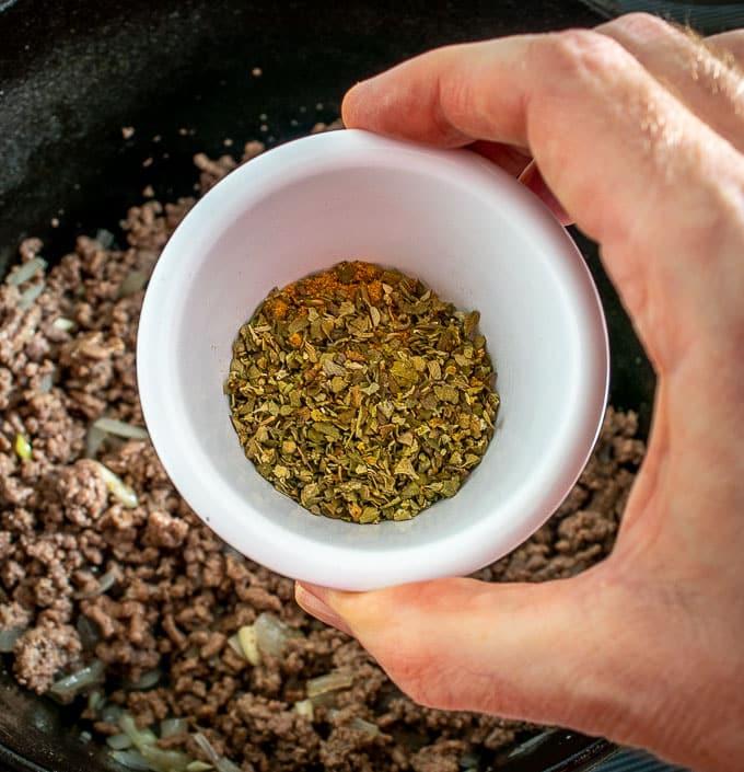 Adding Mexican oregano and cumin