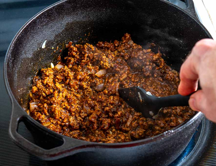 Mixing the chile puree with the ground beef mixture