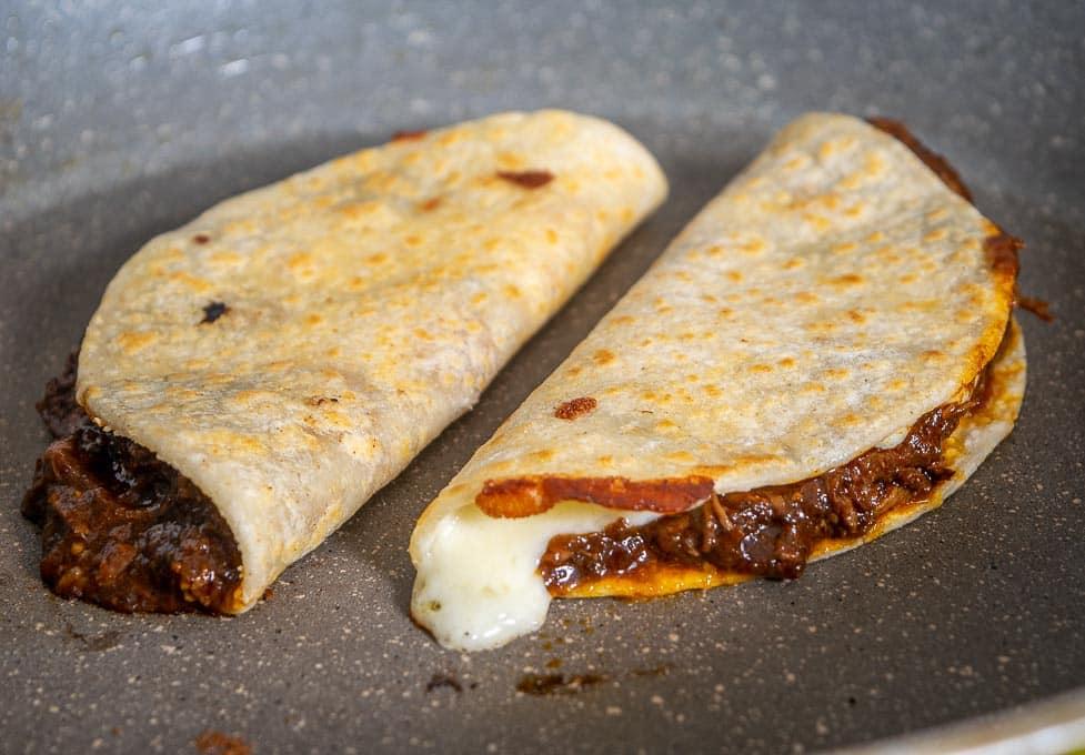 Birria tacos folded in half in the skillet