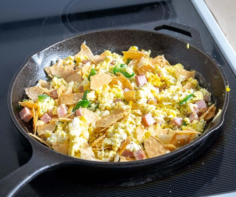 Adding crumbled corn tortillas to the Migas