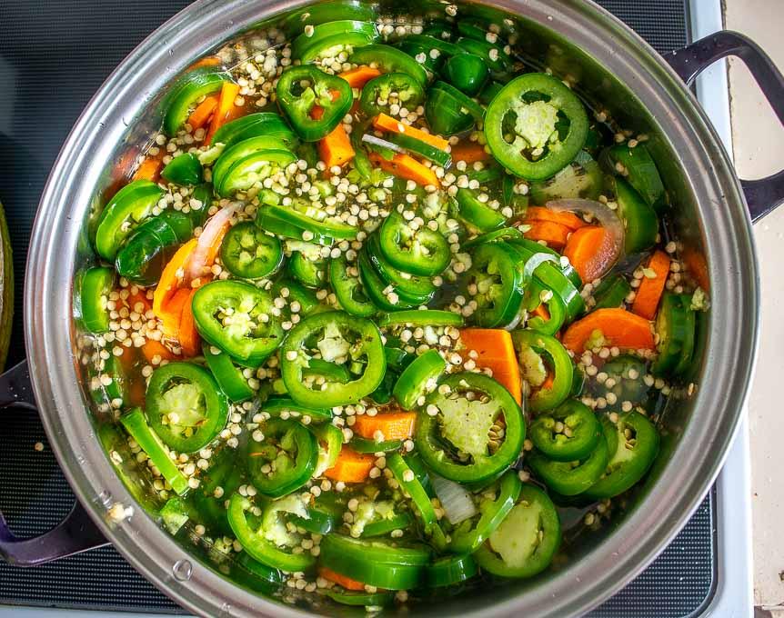 Adding sliced jalapenos to the saucepan