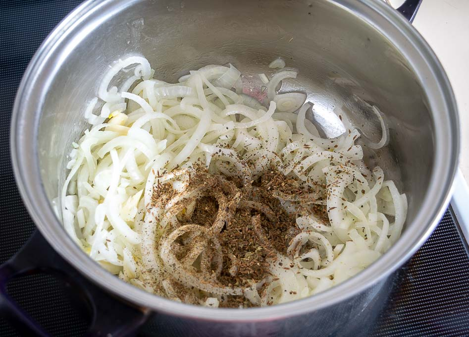 Adding crushed spices to the onions