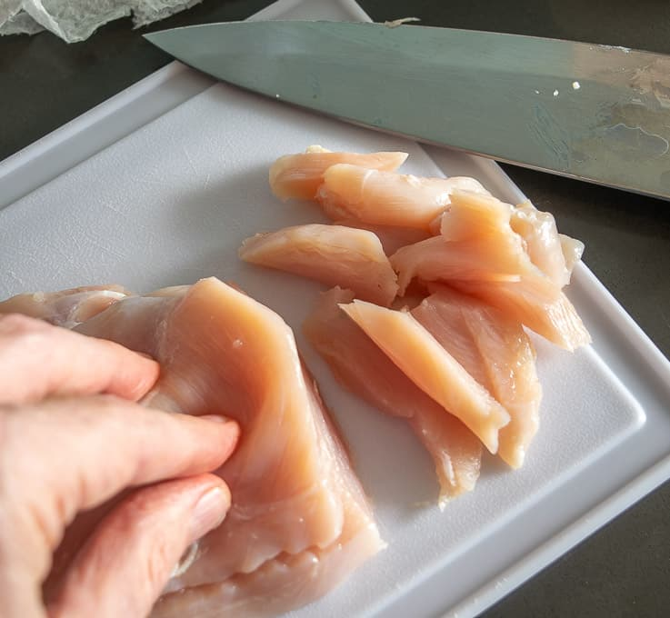 Chopping chicken into bite-sized pieces