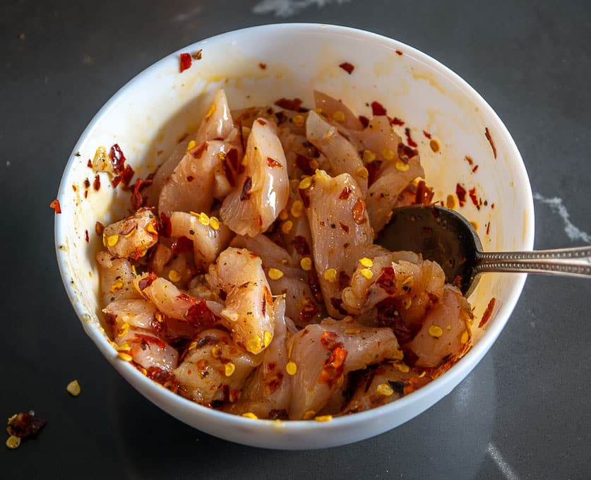 Combining the chopped chicken with salt, pepper, chile powder, and olive oil